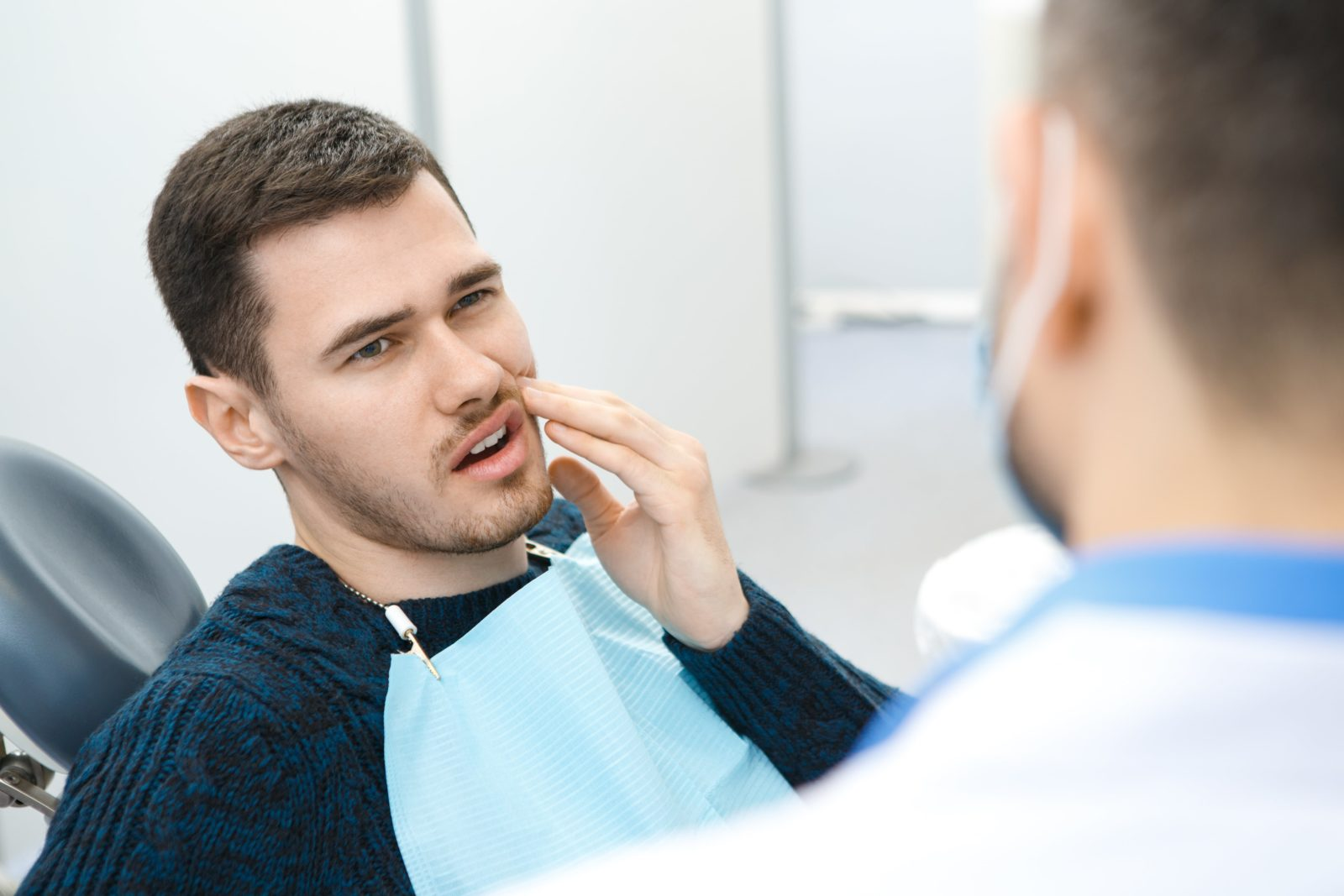 man with toothache talking to dentist